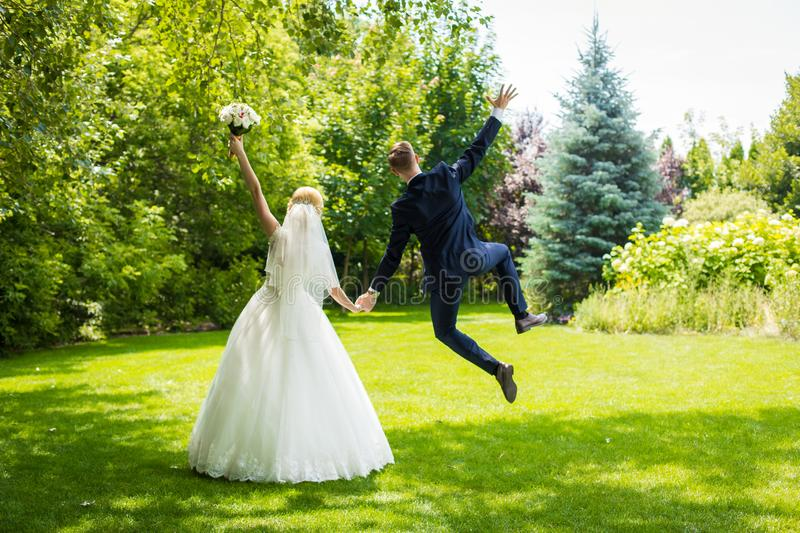 Happy newlyweds rejoice and jump on a green lawn. Wife white wedding dress, groom in a suit.  stock photo