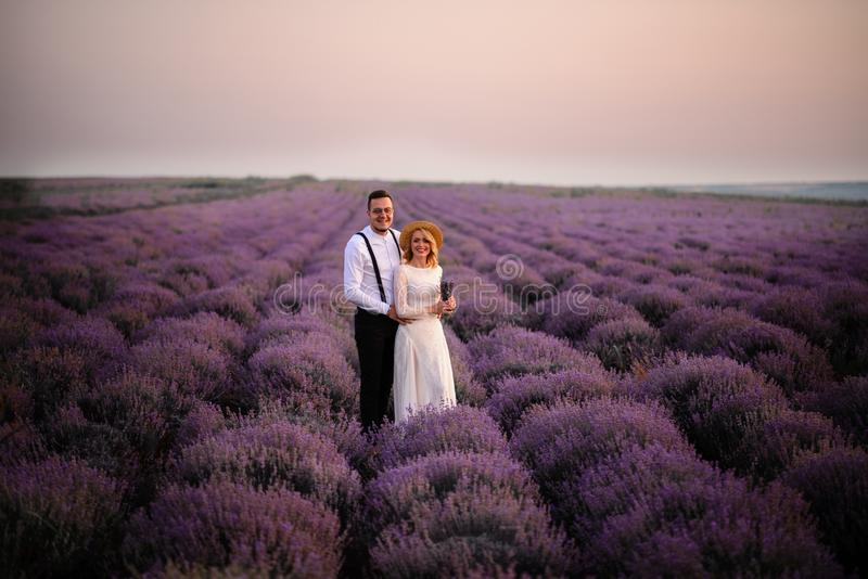Happy newlyweds stand in blooming lavender field at sunset stock photography