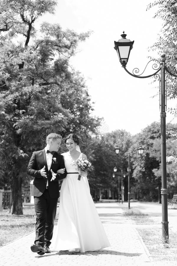 Happy newlyweds walking outdoors. Black and white effect stock photography