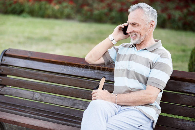 Happy nice-looking senior citizen smiling while talking on the phone. Day-off. Handsome aged male relaxing on a bench in green summer park royalty free stock images