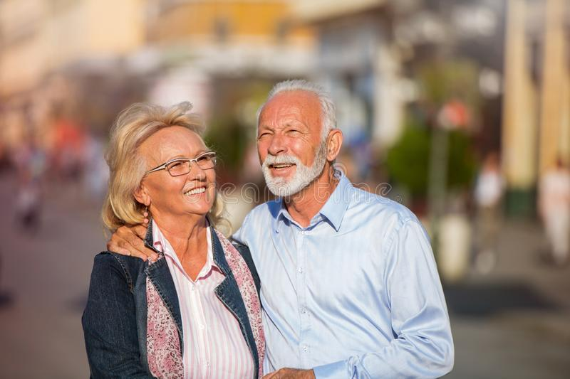Happy nice mature couple walking in town stock images