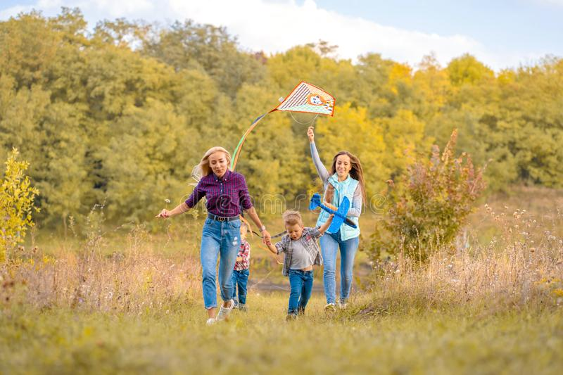 Happy non traditional family of two young mother and their kids launch a kite on nature at sunset stock images