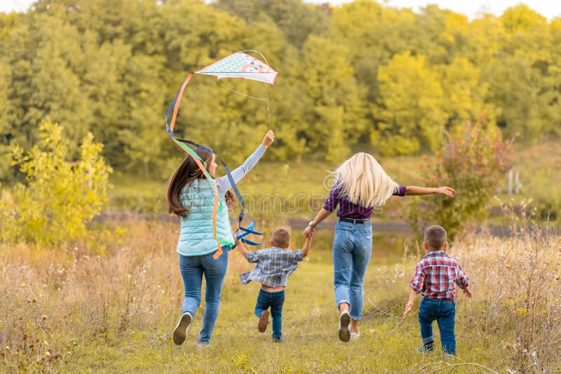 Happy non traditional family of two young mother and their kids launch a kite on nature at sunset royalty free stock photography