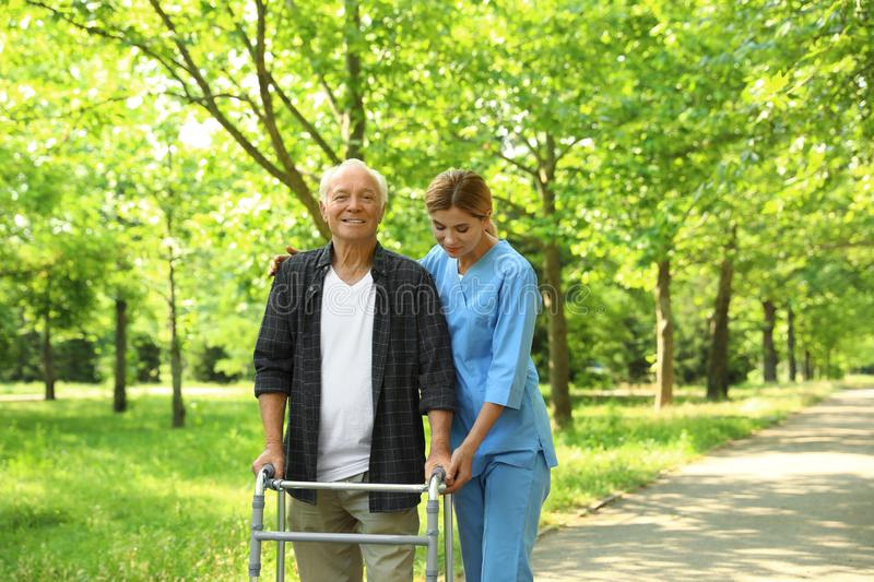 Happy nurse assisting elderly man with walking frame royalty free stock photo