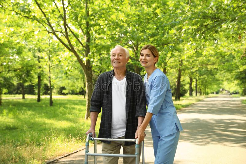 Happy nurse assisting elderly man with walking frame royalty free stock photos