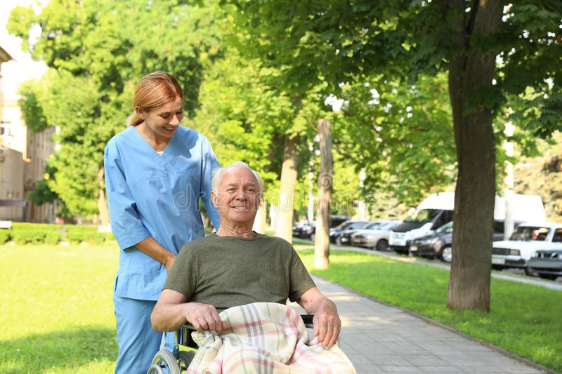 Happy nurse assisting elderly man in  at park stock photography