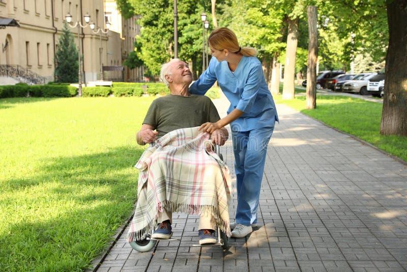 Happy nurse assisting elderly man in wheelchair stock photo