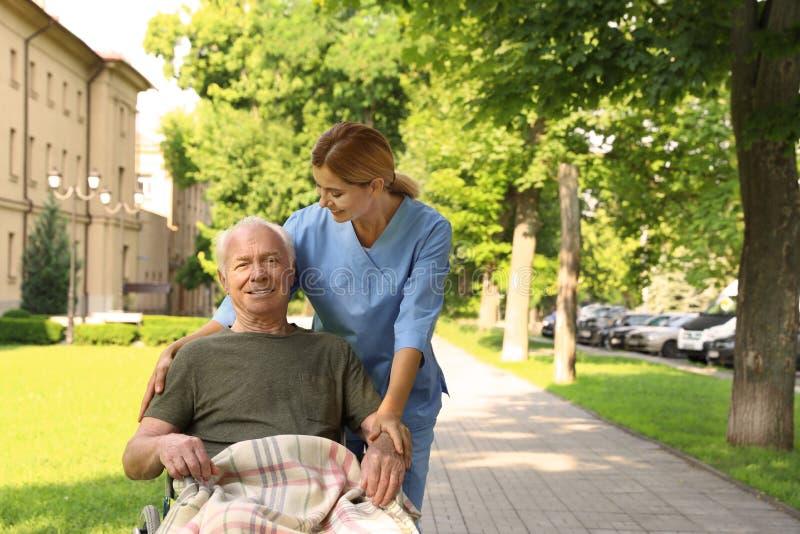 Happy nurse assisting elderly man in wheelchair stock photography