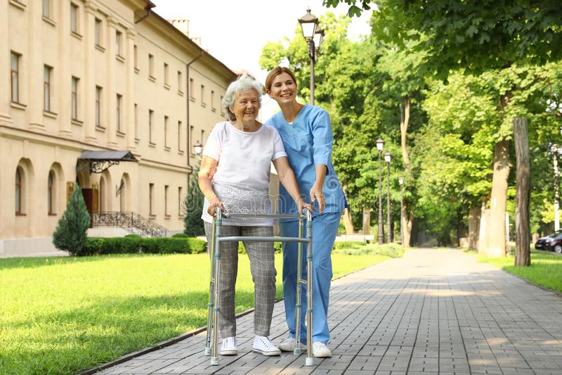 Happy nurse assisting elderly woman with walking frame royalty free stock photography