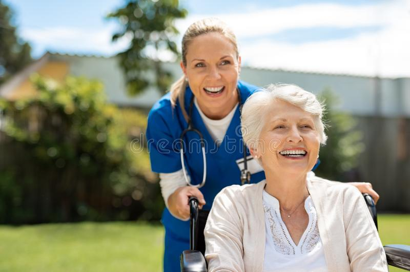 Woman on wheelchair having fun with nurse stock images