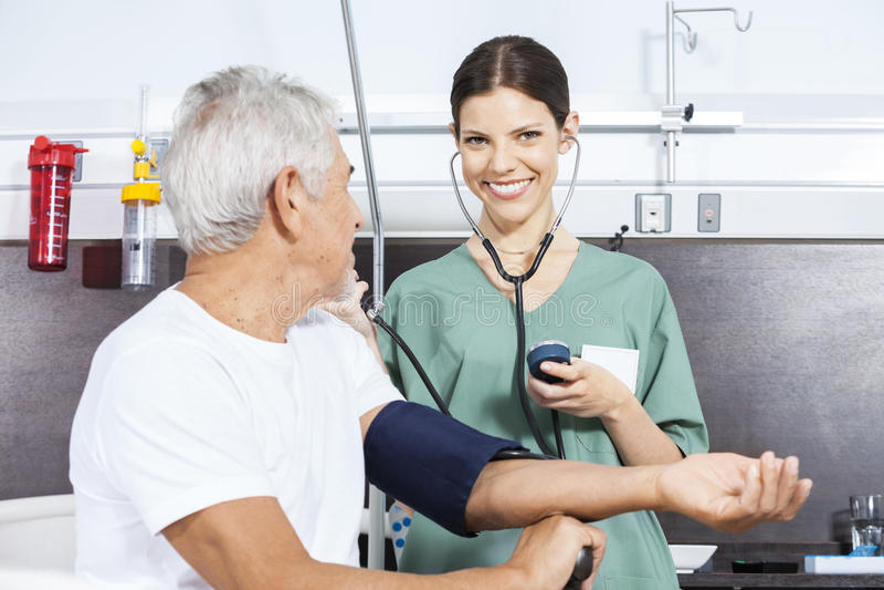 Happy Nurse Examining Blood Pressure Of Man In Rehab Center. Portrait of happy female nurse examining blood pressure of senior men in rehab center stock photography