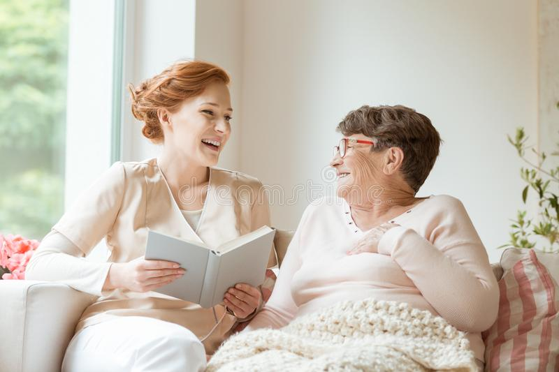 Happy nurse reading a funny book to her elderly patient in a private nursing home stock photography
