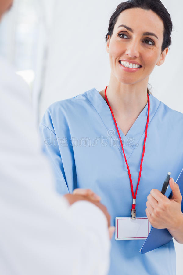 Happy nurse shaking hands with doctor stock photography