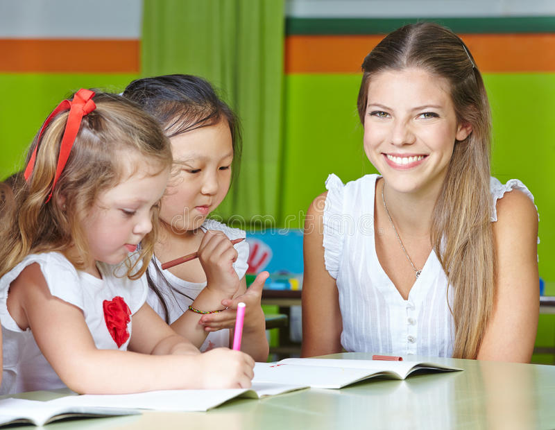 Happy nursery teacher with kids royalty free stock photography