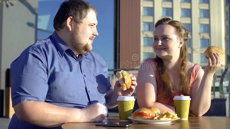 Happy obese couple eating hamburgers on romantic date, flirting in outdoor cafe royalty free stock photo