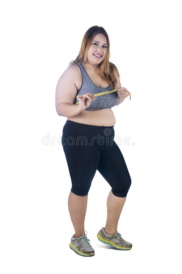 Happy obese woman measures her chest on studio. Full length of obese woman looks happy while measuring her chest with measuring tape, isolated on white stock photography