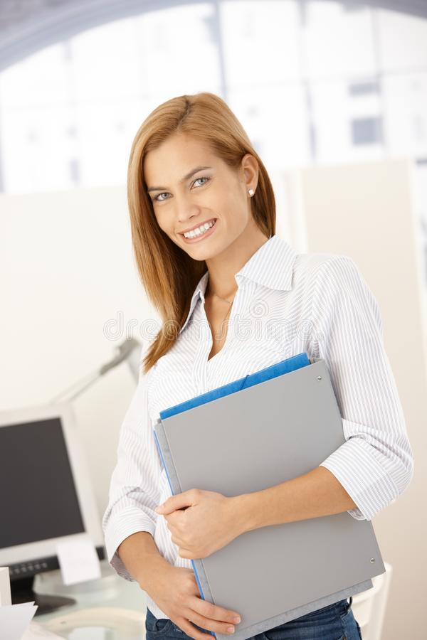 Happy office girl with folders. Happy office girl standing with folders handheld, smiling at camera stock photos