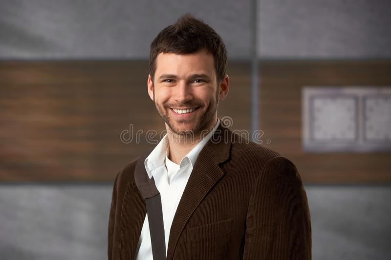 Happy office worker. Standing in office lobby, smiling at camera royalty free stock photo