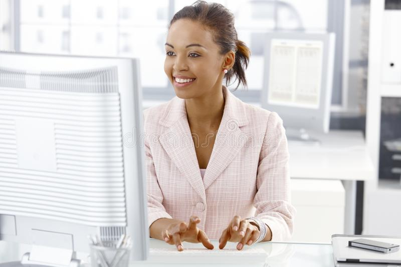 Happy office worker girl at desk. Happy office worker girl sitting at desk, working on computer, looking at screen stock image