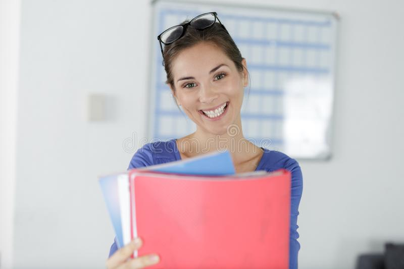 Happy office worker holding forward folders. Happy office worker holding forward some folders stock images