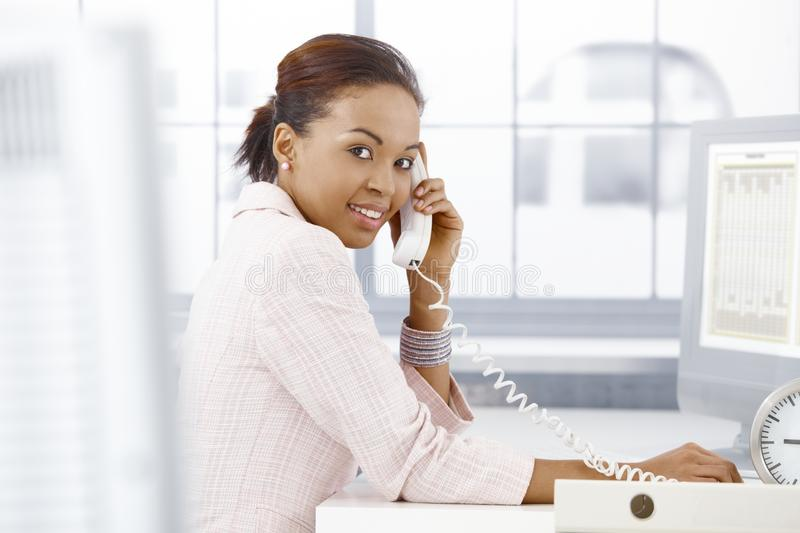 Happy office worker on phone. Happy ethnic office worker speaking on landline phone, smiling at camera royalty free stock photos