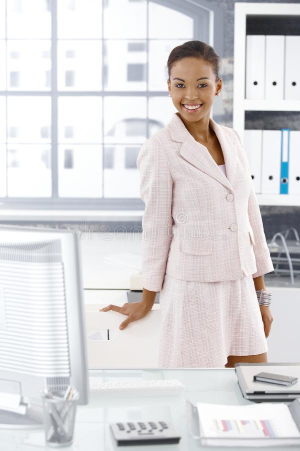 Happy office worker posing. Happy office worker girl posing at desk, smiling at camera stock images