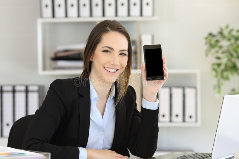 Office worker showing a phone creen mockup stock photography