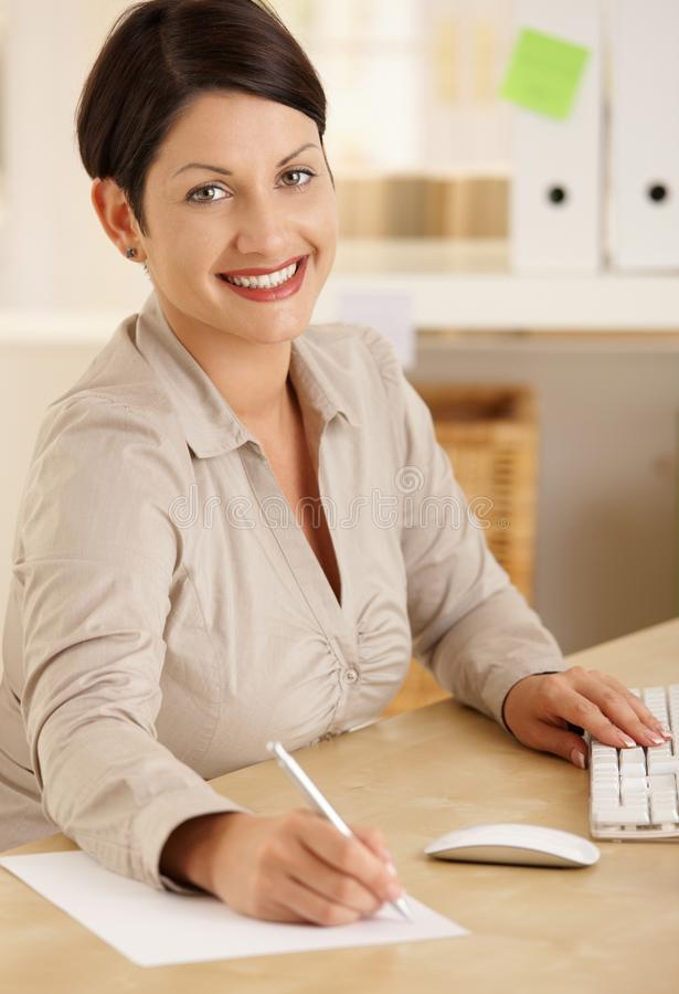 Happy office worker taking notes. Happy office worker working at desk writing notes. Looking at camera, smiling stock images