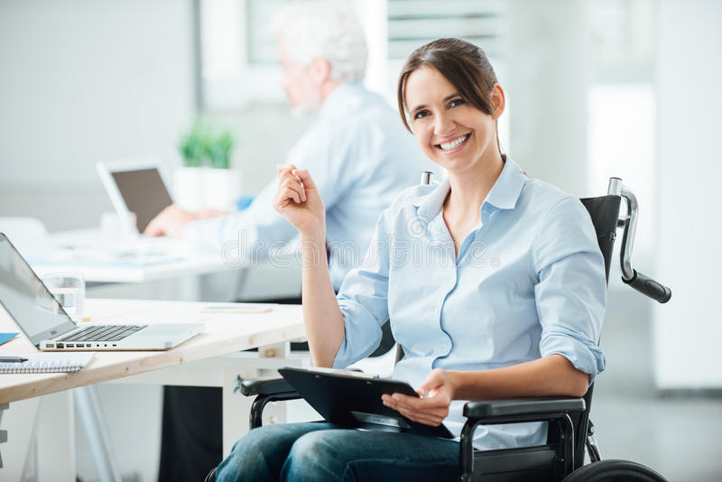 Happy office worker in wheelchair. Happy female office worker in wheelchair holding a clipboard and smiling at camera, disabled people support at workplace royalty free stock images