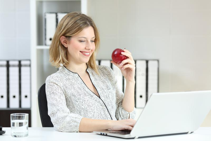 Happy office worker working holding an apple. Happy office worker working online with a laptop holding an apple royalty free stock photo