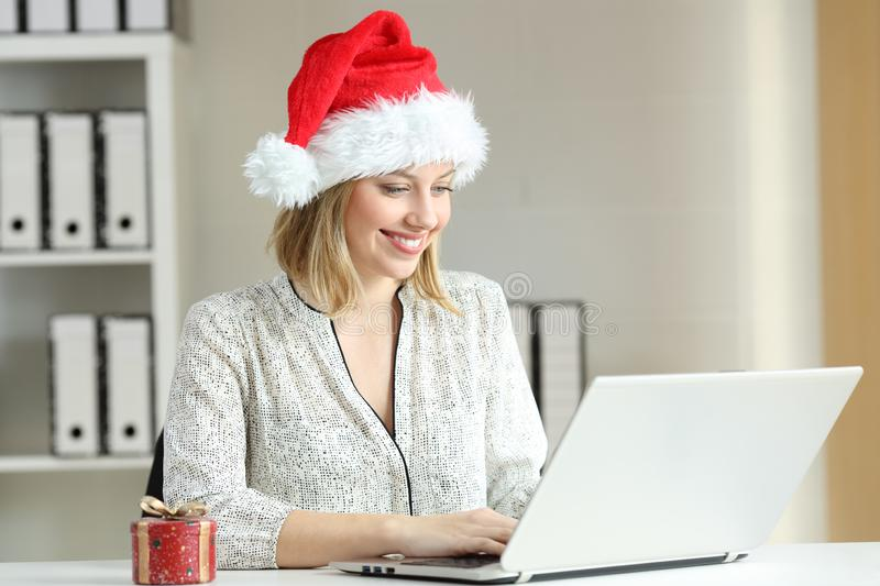 Office worker working in christmas time. Happy office worker working on line with a laptop in christmas time stock image