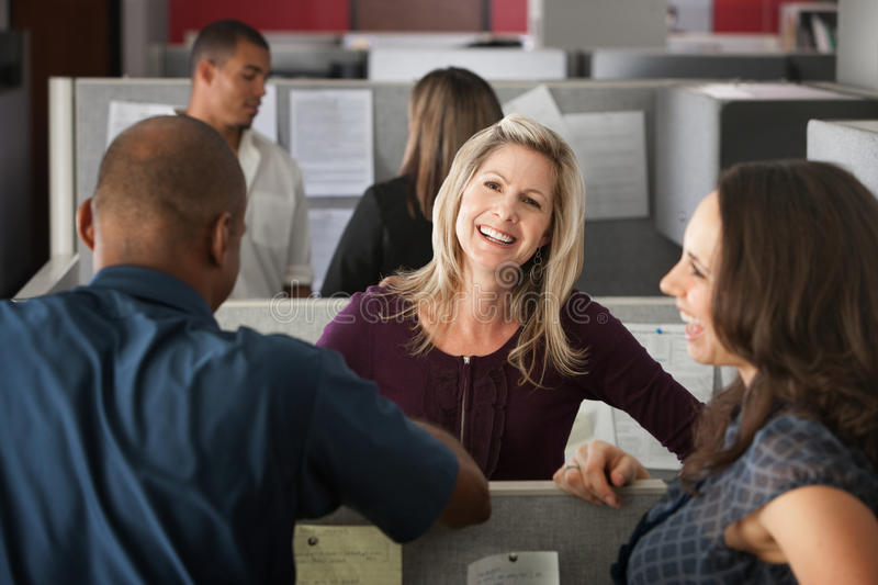 Happy Office Workers. Office workers laugh at a joke shared by colleague stock image