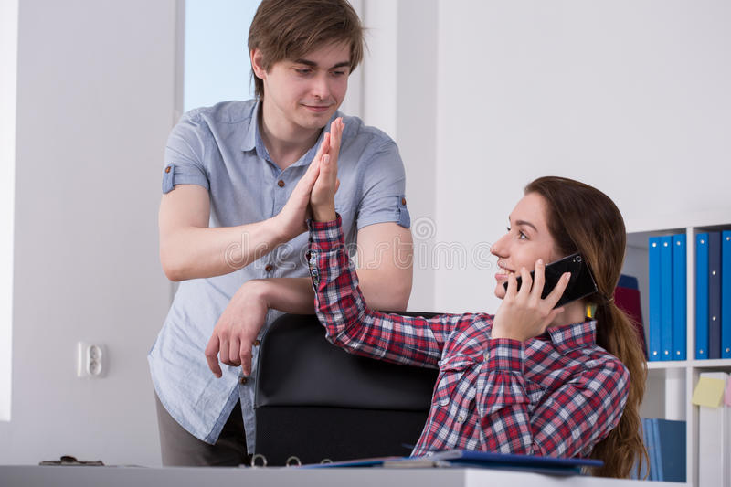 Happy office workers. Photo of happy office workers making high five royalty free stock photography