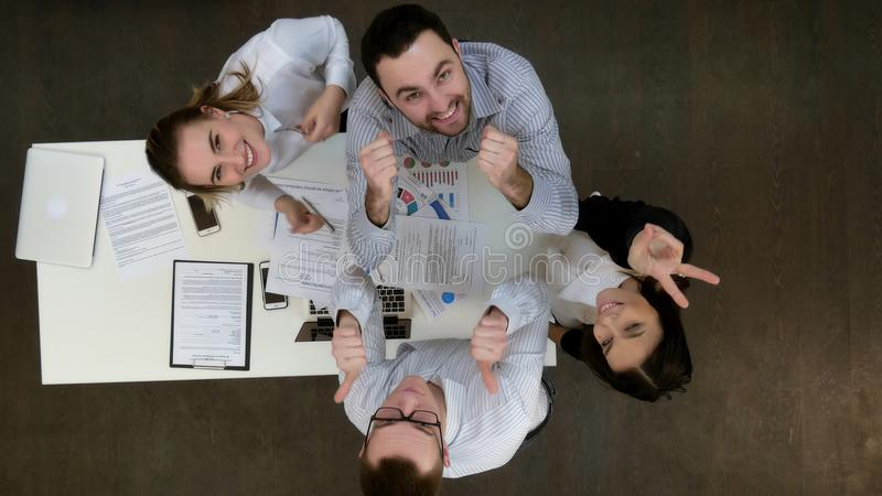 Happy office workers smiling to the camera and showing thumbs up royalty free stock image