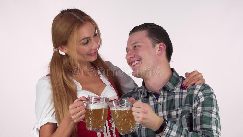 Happy Oktoberfest couple clinking beer mugs, smiling at each other stock images