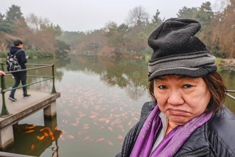 Happy old asian women traveler make a funny face in the xihu lakewest lake stock photo