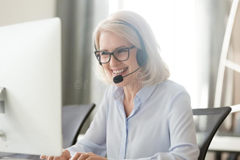 Happy old businesswoman in headset making call looking at computer. Happy old businesswoman in headset speaking by conference call looking at computer, mature stock images