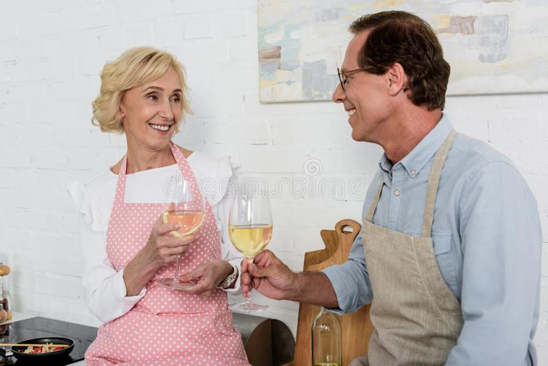 happy old couple in aprons holding glasses of wine and smiling each other royalty free stock photo