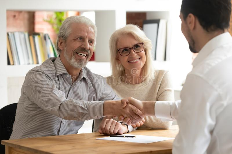 Happy old couple clients make financial deal handshake meeting lawyer. Happy senior old family couple clients make financial insurance estate business deal royalty free stock photo
