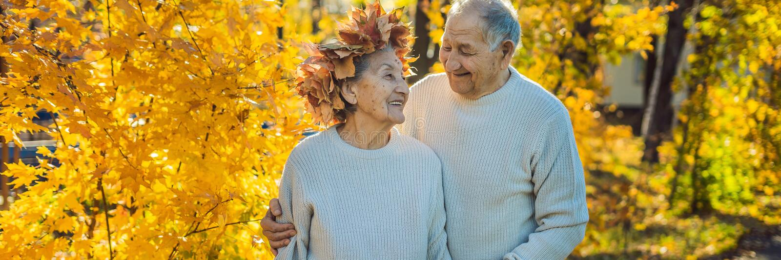 Happy old couple having fun at autumn park. Elderly man wearing a wreath of autumn leaves to his elderly wife BANNER. Happy old couple having fun at autumn park stock photo