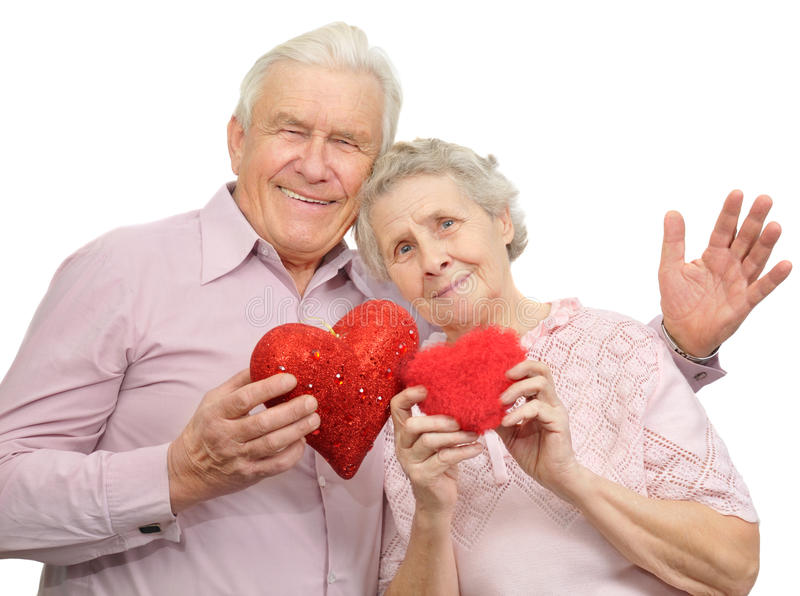 Happy old couple with red hearts stock photography