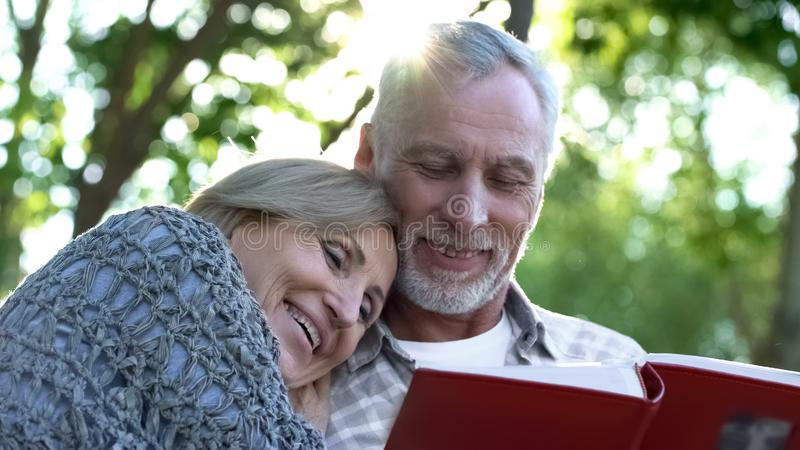 Happy old couple watching photobook and smiling, pleasant youth memories, fun royalty free stock images