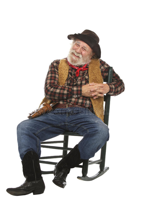Happy old cowboy sits in rocking chair stock images
