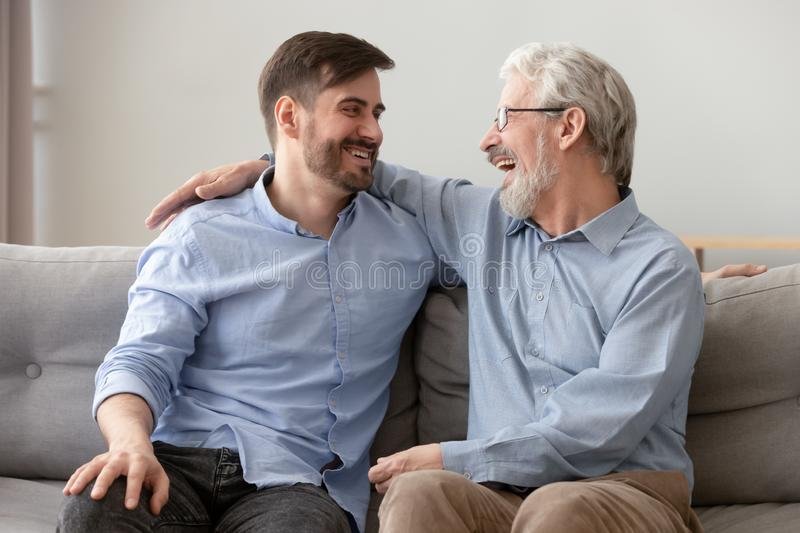 Happy old dad embracing young son talking laughing on sofa. Happy old senior dad embracing young adult grown son talking laughing sit on sofa at home at reunion royalty free stock photo