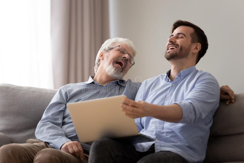 Happy old father and young son laughing using laptop together. Happy male two generations family, old senior father and positive young grown adult son bonding royalty free stock photo