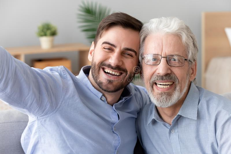 Happy old father young son take selfie, mobile camera view. Happy two generations men old father laughing embracing young son take selfie shoot vlog together on royalty free stock photo