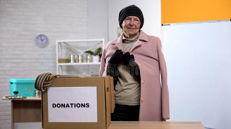 Happy old homeless woman looking camera, donations box table, humanitarian aid stock photo