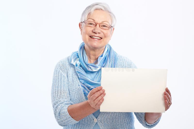 Happy old lady with blank sheet. Happy elderly lady holding blank sheet in hand, smiling royalty free stock images
