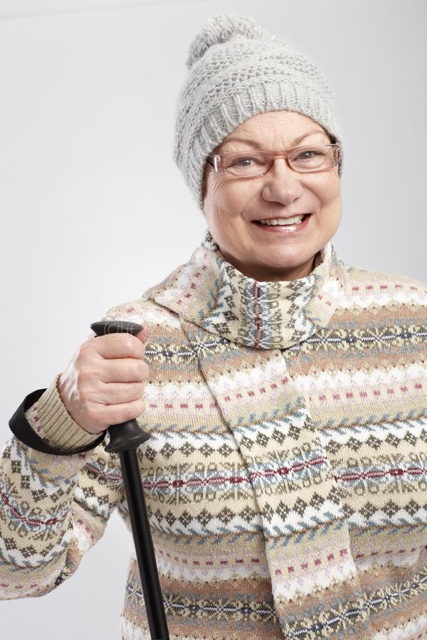 Happy old lady hiking. Happy old lady in winter clothes hiking, smiling royalty free stock photo
