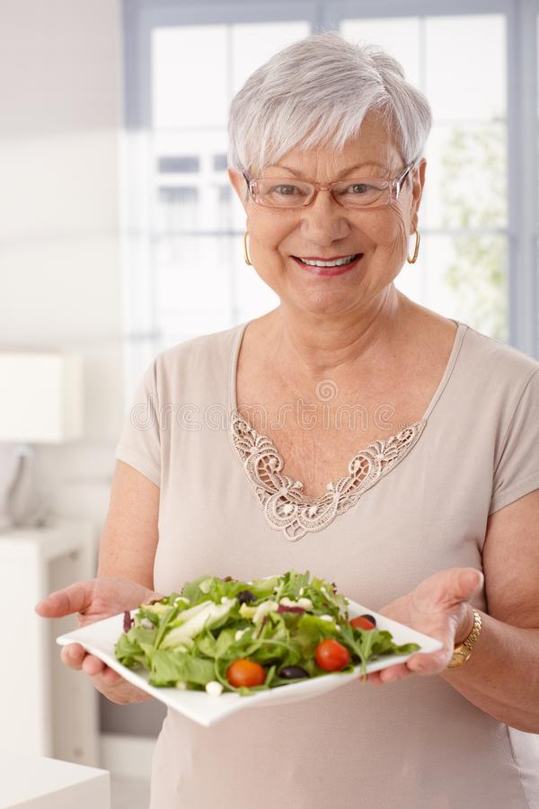 Happy old lady holding fresh green salad. Happy old lady holding plate of fresh green salad, looking at camera royalty free stock photo